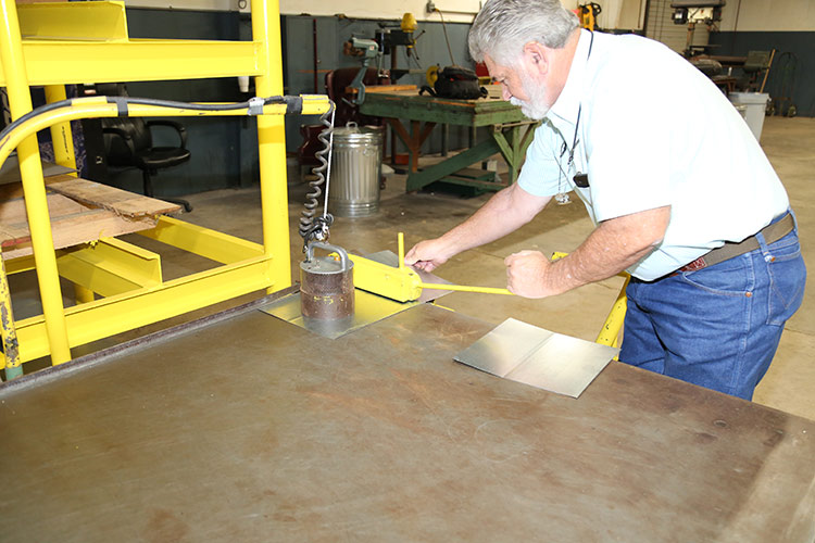 Jim Patterson, owner, working on a machine.