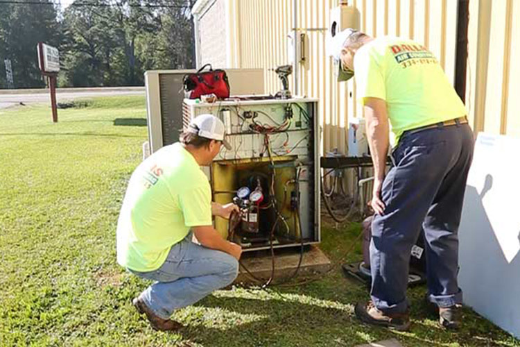 Employees working on air conditioning unit.